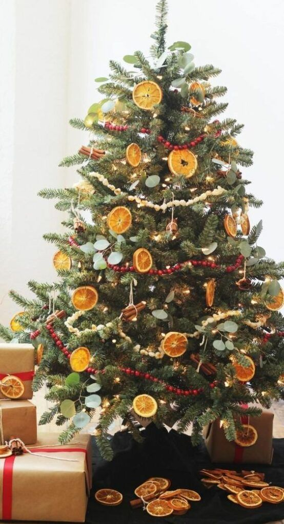 Citrus Dried Fruit - 20 Gorgeous Christmas Tree Decoration Ideas To Try This Year: Using food in different ways as decoration for you Christmas tree is a fun and sustainable way for creating decor pieces. Using dried slices of oranges and citrus fruit and stringing popcorn and berries to make garlands around the tree for a traditional and festive look. @chloedominik #christmastreeideas #christmastreedecorations #christmastreedecorideas #foodiechristmastree #traditionalchristmastreedecor
