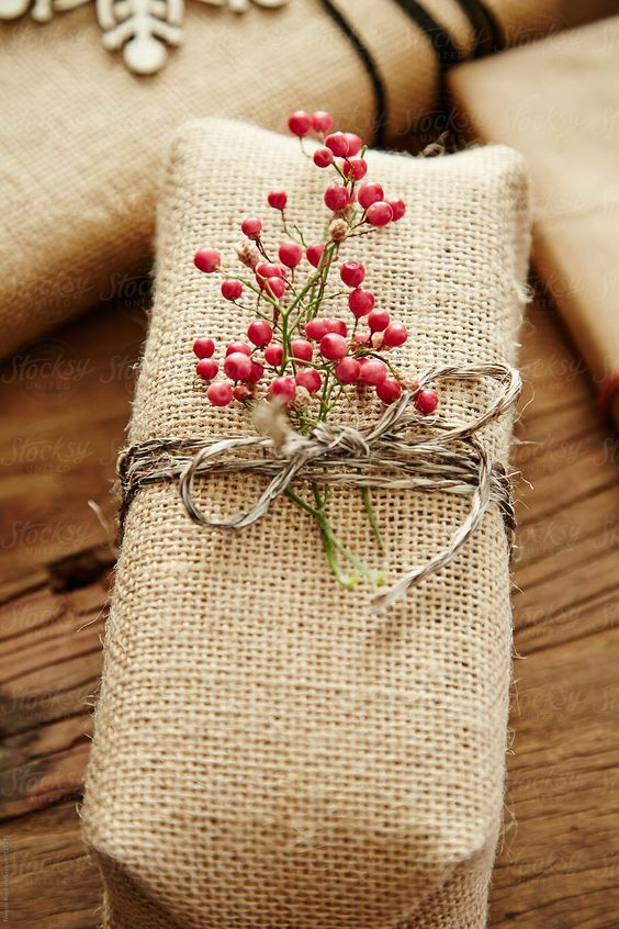 Hessian Wrap Tied With Berries - 20 Creative Ways To Gift Wrap Your Presents This Christmas: A rustic style of wrapping only needs simple materials to make that gift a little extra special. Like this hessian material wrapped gift tied with twine and finished with a red berry sprig. @chloedominik #wrappingideas #giftwrapping #giftwrappingideas #giftwrappinginspiration #christmaspresentideas #creativegiftwrapping