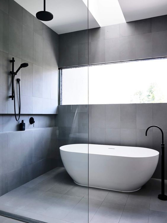Contemporary Grey Wet Room - Amazing Wet Room Ideas: Top 12: A contemporary wet room with a minimal aesthetic clad in grey large tiles with natural light. The bathroom is finished with black shower fixtures. @chloedominik #greybathroom #contemporarywetroom #wetroomideas #minimalbathroomdesign #minimalwetroom #greyandblackbathroom