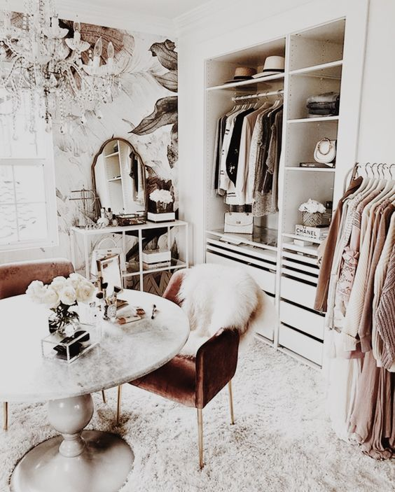 Glamorous Dressing Room - 16 Amazing Stylish Wardrobe Ideas That Use The Ikea Pax: A stunning dressing room design complete with chandelier uses the Ikea pax closet system for organizing clothes and displaying the favourite items in open shelving section. The decorative wallpaper and cozy furnishings make the walk in closet an elegant space to get ready in. @chloedominik #walkincloset #walkinwardrobe #dressingroomideas #dressingroomdesign #glamorousclosetwalkin #elegantdressingroom