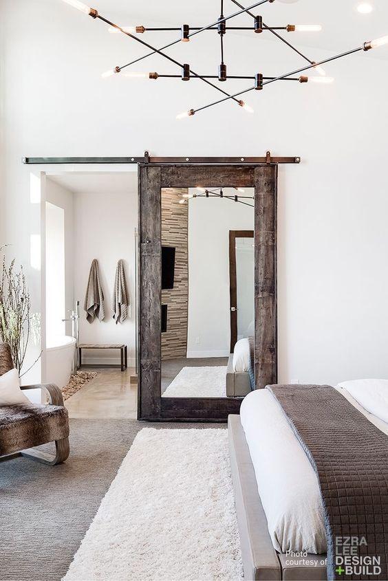 Mirrored Barn Door Dividing Bathroom From Bedroom