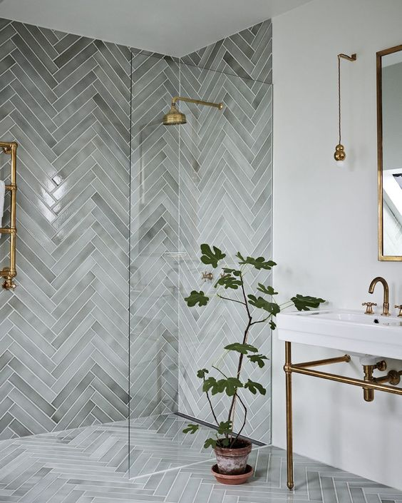 A beautiful herringbone tiled wet room shower walk in. Decorated with neutral coloured tiles and finished with gold accents and shower fixtures. #wetroombathroom #herringboneshowertile  #brassaccentsbathroom #wetroomshowerwalkin