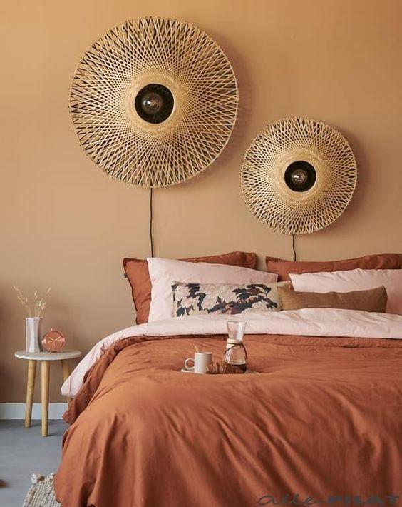 Warm terracotta colour tones in the bedroom create a Mediterranean cozy feel interior with rattan lighting decor on the wall. #terracottacolorpalette #terracottabedroom #warmcolorforbedroom #mediterraneanbedroom #rattanlightfixture @chloedominik