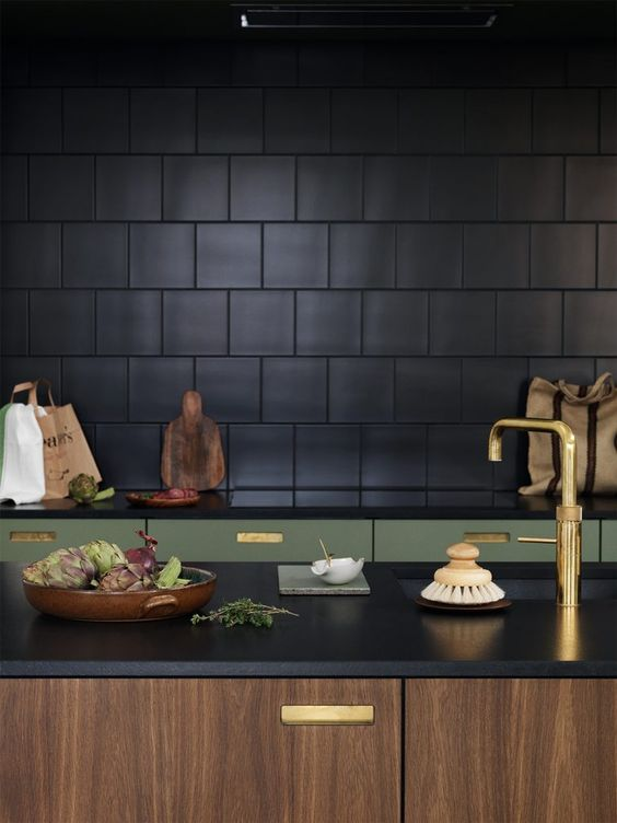 An elegant and luxury designed kitchen using black tiles for the backsplash and rich walnut and olive green for the lower cabinets, continuing the black across the countertops and gold finishes for the hardware. The ultimate luxury kitchen design. #blackkitchen #blacktiledkitchen #luxurykitchendesign #luxurykitchen #blackkitchencountertops @chloedominik