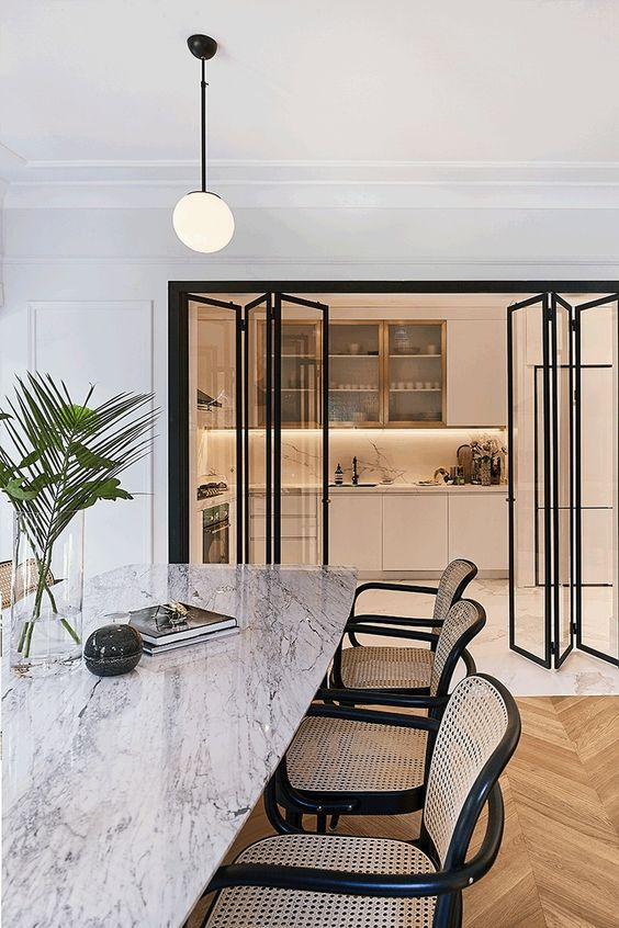 Modern Bi-Folding Kitchen Doors - 8 Great Reasons For And Against Open Concept Living: This interior uses modern black metal bi-folding doors between the kitchen and the dining area which creates a great balance between open concept living in the home. Interior design unknown. #modernkitchendiningarea #bifoldingdoorskitchen #bifoldingdoorsdiningroom #modernbifoldingdoors #openconceptliving #openconcepthome #openconcepthomedesign