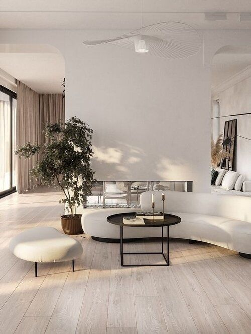 Modern White Living Room -The Curved Sofa: 4 Reasons Why The Interior Trend Is Taking Over: A beautiful modern white living room that makes the most of the space by featuring a gorgeous white curved sofa to the interior design makes it more luxurious and modern. Adding open set furniture which expands the living room area even more. @chloedominik #modernlivingroom #whitelivingroom #modernwhitelivingroom #curvedsofalivingroom #curvedsofalivingroominteriordesign