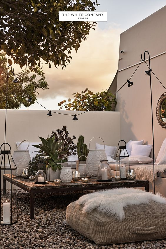 The White Company Outdoor Courtyard Seating Area - Using Garden Lanterns: 10 Favourites: A beautiful courtyard garden hosting idea from The White Company campaign. Using a score of lanterns as a decorative table scape as the central focal point of the seating area. @chloedominik #lanterns #lanternsdecor #gardenlanterns #gardenpartydecorations #gardenlanternoutdoor #gardenlanternideas #gardenlightingideas #thewhitecompany #courtyardgardenideas
