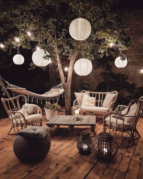 Boho Lantern Garden Setup - 9 Essentials For Hosting The Perfect Garden Party: A gorgeous boho night party decorated with Chinese lanterns from the tree and floor lanterns to set the atmosphere. Wicker seating with large cushions is the perfect place to lounge out and chat. @chloedominik #gardenparty #gardenpartyideas #gardenpartydecor #hostingagardenparty #gardenpartyessentials #paperlanternsgardenparty