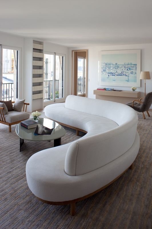 Sleek White Curved Sofa: The Curved Sofa: 4 Reasons Why The Interior Trend Is Taking Over: With a big living room space you have the option to go for a bigger sofa like this sleek curved sofa which will seat a lot people. It's scale is in proportion to the room and the curve adds a sculptural element to the interior design. @chloedominik #curvedsofa#curvedsofalivingroom #curvedsofasinlivingrooms #curvedsofadesign #curvedsofadesignideas