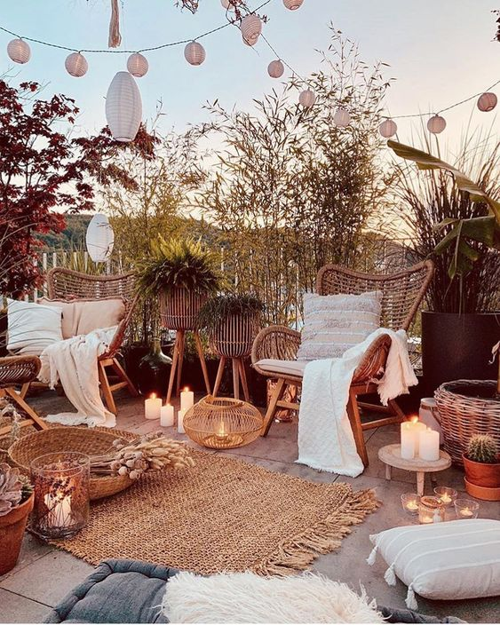 Beautiful Boho Outdoor Space - 9 Essentials For Hosting The Perfect Garden Party: A beautifully decorated outdoor space hung with lighting and lanterns above and plenty of seating ranging from wicker chairs and throw cushions on the ground, perfect idea for a garden party. Candles add to the boho styled space and cozy throws for the guests. @chloedominik #gardenparty #gardenpartyideas #bohogardenparty #bohogardenpartyideas #bohogardenpartydecoration #gardenpartyessentials #hostingagardenparty