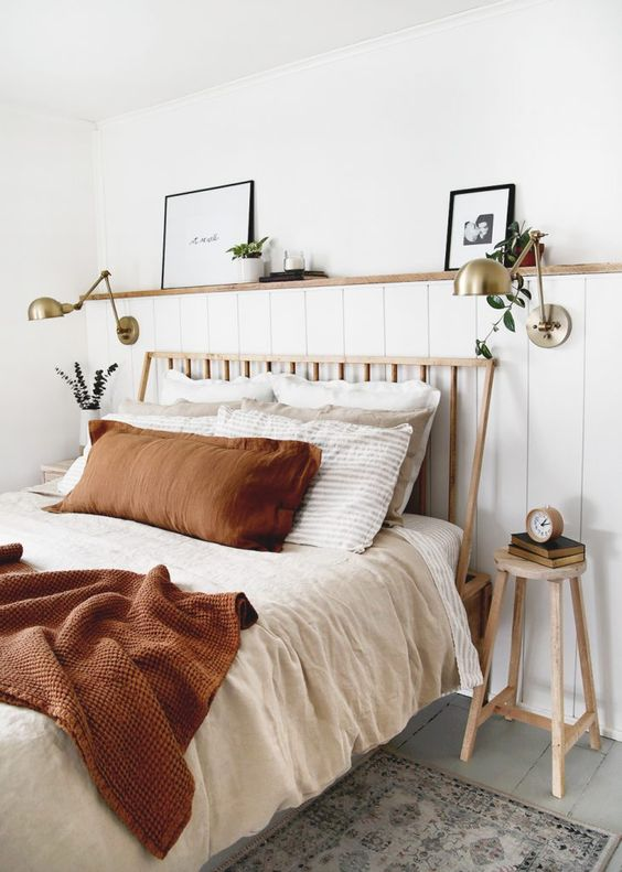 Beautiful Relaxed Bedroom: 7 Simple Daily Tasks To Keep Your Home Organized: A simple and beautifully styled bedroom interior bringing warm white neutrals together with a styled bed in a spiced burnt orange colour. A built in ledge hosts favourite photos and brass light sconces. @chloedominik #relaxedbedroominterior #neutralbedroomideas #bedroomledgedecor #styledbed