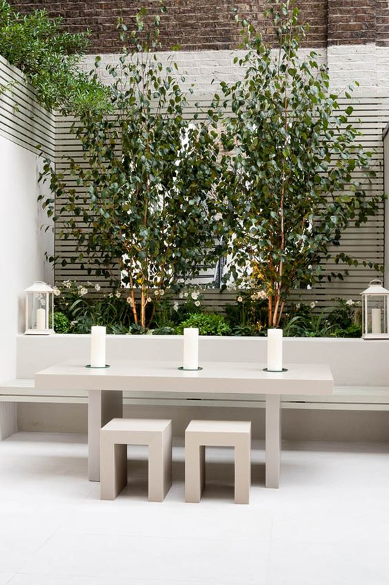 Modern Small Garden Courtyard - July Pinterest 2020: Top 15 Inspiration & Ideas: A small outdoor space that is transformed in to a beautiful white garden courtyard with a built in bench seat and dining area and lots of greenery which make a beautiful contrast against the white walls. Design by Karen Rogers @chloedominik #gardencourtyardideas #whitegardenwall #smallgardencourtyard #gardendiningarea #gardendesign