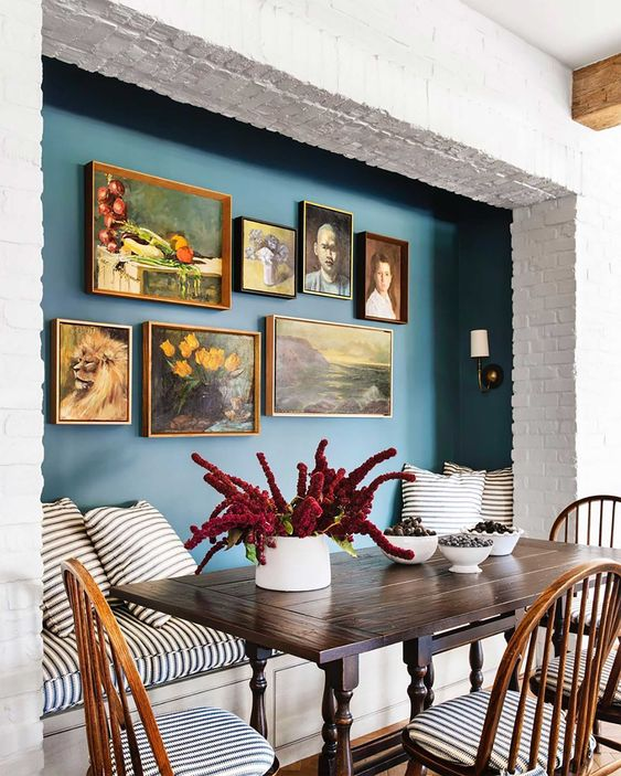 Bold Gallery Feature Wall Breakfast Nook - July Pinterest 2020: Top 15 Inspiration & Ideas: The bold teal colour makes an impact in leaping out from the white brick wall to bring attention to the gallery feature wall adorning the breakfast nook. Design by Molly Brit Design. @chloedominik #gallerywallideas #boldgallerywall #breakfastnook #breakfastnookideas