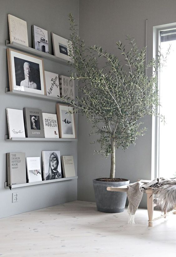 Modern Grey Book Ledge Gallery Wall - 7 Ways To Decorate An Empty Corner At Home: Creating a corner book ledge gallery wall is a modern and stylish way to display decor and to mix up your ledge wall with frames and books. Or you can dedicate it to one use of either a mini library entirely or simply for display. Beautiful either way. @chloedominik #bookledgegallerywall #emptycorner #emptycornerideas #ledgewalldecor #ledgewalldecoratingideas #modernledgedecor