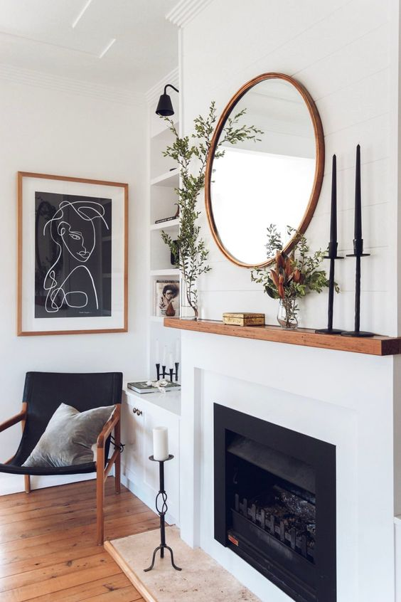Modern Fireplace Focal Living Room - 10 Interior Design Mistakes And How To Fix Them: A beautiful modern fireplace for the focal point in the living room in simple white and black with warm wood mantel with the wood accents repeated through out the living room. @chloedominik #modernlivingroom #modernlivingroomdecor #fireplacelivingroom #fireplacelivingroomdecor #blackandwhitelivingroomideas #interiordesigntips #interiordesignmistakes