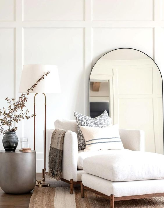 Cozy Living Room Corner - July Pinterest 2020: Top 15 Inspiration & Ideas: A calming white neutral styled living room corner with panelled walls decorated with curved mirror and cozy armchair to curl up for relaxing with a floor lamp and side table. @chloedominik #cozylivingroomcorner #cozylivingroomcornerideas #styledlivingroom #panelledwallslivingroom #styledcorner