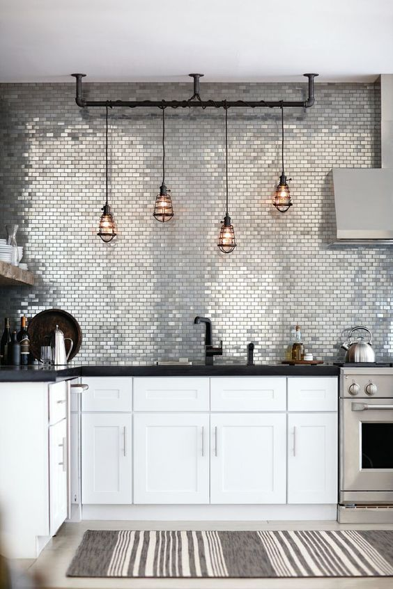 Stainless Steel Backsplash - 6 Great Marble Alternatives For Around Your Home: A stainless steel tiled backsplash going full height to the top of the wall. The reflective tile brings high impact and bounces light around the kitchen area creating a modern and industrial kitchen design. @chloedominik #stainlesssteelbacksplash #stainlesssteelbacksplashkitchen #marblealternative #marblealternativewall #marblealternativecountertops #interiortrends