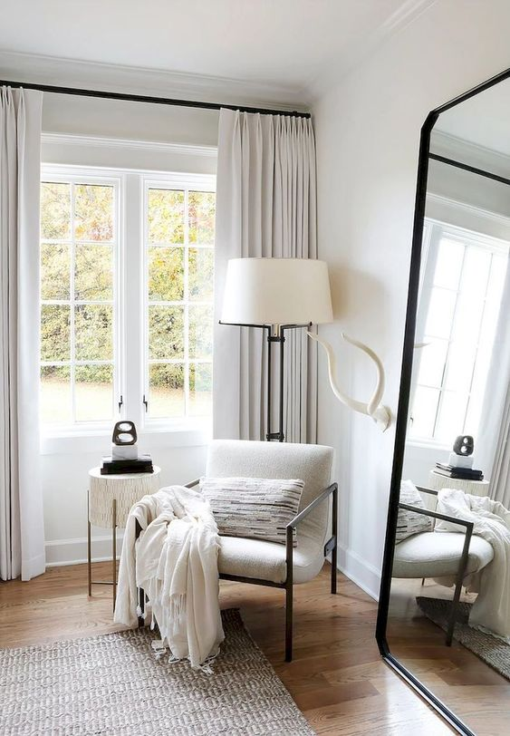 Calming White Bedroom Styled Corner - 10 Interior Design Mistakes And How To Fix Them: A beautiful styled bedroom corner all in white with black finishes around the room makes the most of the ceiling height by hanging the pleated white curtains as high as possible giving it a look of elegance. @chloedominik #whitebedroomcorner #whitebedroomcornerideas #whitepleatedcurtains #whitestyledbedroom #interiordesigntips #interiordesignmistakes #calmingbedroom