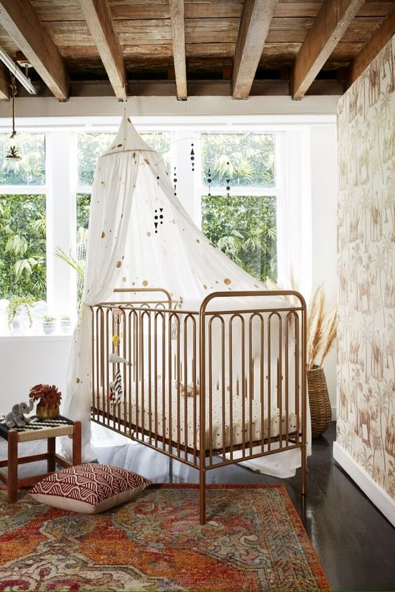 Lovely Boho Nursery Room - July Pinterest 2020: Top 15 Inspiration & Ideas: A lovely nursery room done in a classy boho style with a beautiful accent wall and bronze railed crib decorated with muslin and mobiles above the crib. A beautiful room for either a baby boy or baby girl. @chloedominik #bohonursery #bohonurseryneutral #nurseryideas