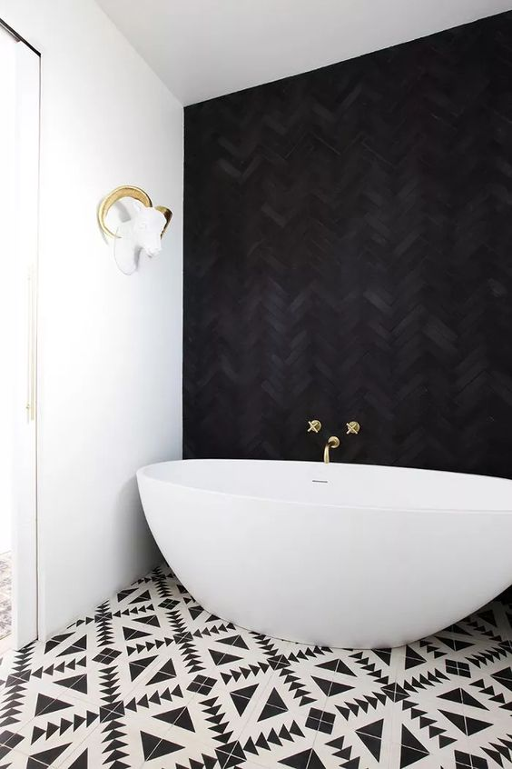 Modern Black & White Monochrome Bathroom - August Pinterest 2020: Top 15 Inspiration & Ideas: Black and white doesn't have to mean boring. This stunning modern and elegant black and white bathroom with geometric black and white floor tiles and a textured black herringbone wall backdrop to the bath tub. @chloedominik #blackandwhitebathroom #modernblackandwhitebathroom #geometrictilesbathroom #blackherringbonewall #monochromebathroom #modernbathroomdesign