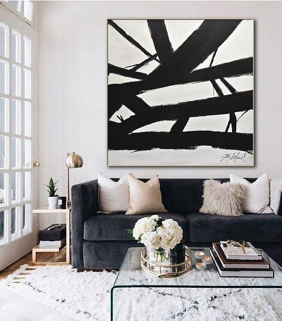 Black Abstract Painting - 12 Tricks To Make Your Living Room Seem Larger: A large black abstract canvas provides a focal point above the sofa, a big canvas in the living room makes the space seem larger. @chloedominik #abstractcanvas #livingroomideas #artcanvaslivingroom #blackandwhitecanvasart