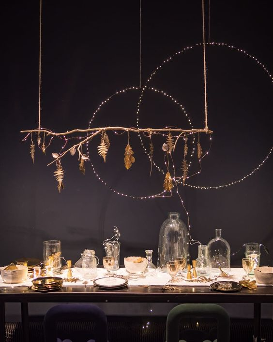 Stunning Christmas Tablescape - September Pinterest 2020: Top 15 Inspiration & Ideas: Simple Christmas decor used in an unusual way creates this stunning Christmas table setting idea. With twinkle lights wrapped around to circle halos above the dining table. Clear and gold dining ware set an elegant tone for the table. @chloedominik #christmastablescapes #stunningchristmastablesettings #christmastablesettings #elegantchristmastablescapes #elegantchristmastablescapesgold