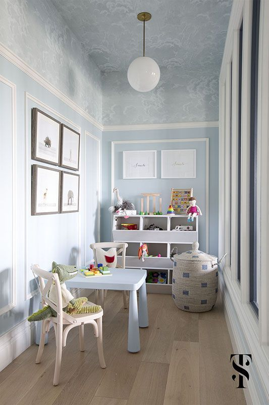 Baby Blue Playroom - 20 Amazing Statement Ceiling Design Ideas For Your Home: A beautiful baby blue kids playroom highlights the ceiling beautifully by using a cloud patterned wallpaper which envelopes the upper walls of the room as well. Design by Summer Thornton Design. @chloedominik #statementceilings #kidsplayroomideas #playroomdesign #wallpaperedceiling #wallpaperedceilingideas #ceilingdesign #ceilingideas