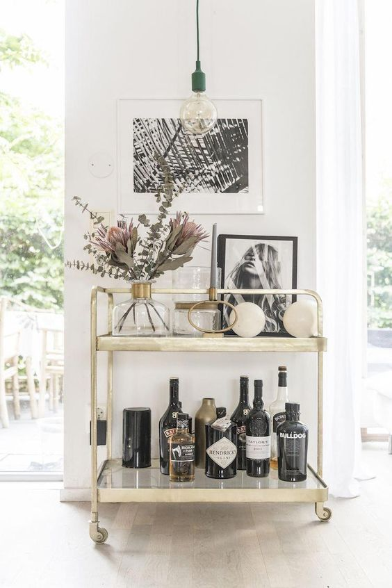 Beautiful Bar Cart Styling - August Pinterest 2020: Top 15 Inspiration & Ideas: Styling a bar cart in your home is a great way to fill an empty space and show some personality with favourite decor items and pieces. Make it a focal point like this modern gold cart styled with bottled drinks, decor and photo frames. @chloedominik #beautifulbarcart #styledbarcart #styledgoldbarcart #barcartdecor #barcartdecorideas