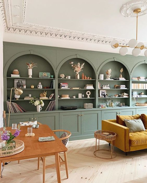 Arched Built Ins Living Room - September Pinterest 2020: Top 15 Inspiration & Ideas: Decorative arched built ins fill the back wall of this living room by Katie La Vie in a gorgeous sage green colour, a great storage idea for a living room space. The room is  finished with modern furniture against the traditional backdrop. @chloedominik #archedbuiltinslivingroom #builtinshelveslivingroom #livingroomideas #livingroombuiltinsdecor #livingroombuiltindecorideas #greenlivingroom