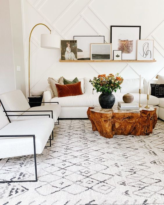 Cozy White Interior Living Room - How To Choose The Right Area Rug: A modern and cozy interior design by Jaci Daily uses a huge area rug in the living room space underneath all the furniture which gives an impression of a bigger space with a white patterned rug and white seating furniture. @chloedominik #howtochoosearug #arearugs #interiordesigntipsrugs #rugsunderdiningtable #choosinganarearug #patternedrug #arearugideas #cozylivingrooms #livingroomrug #livingroomrugideas