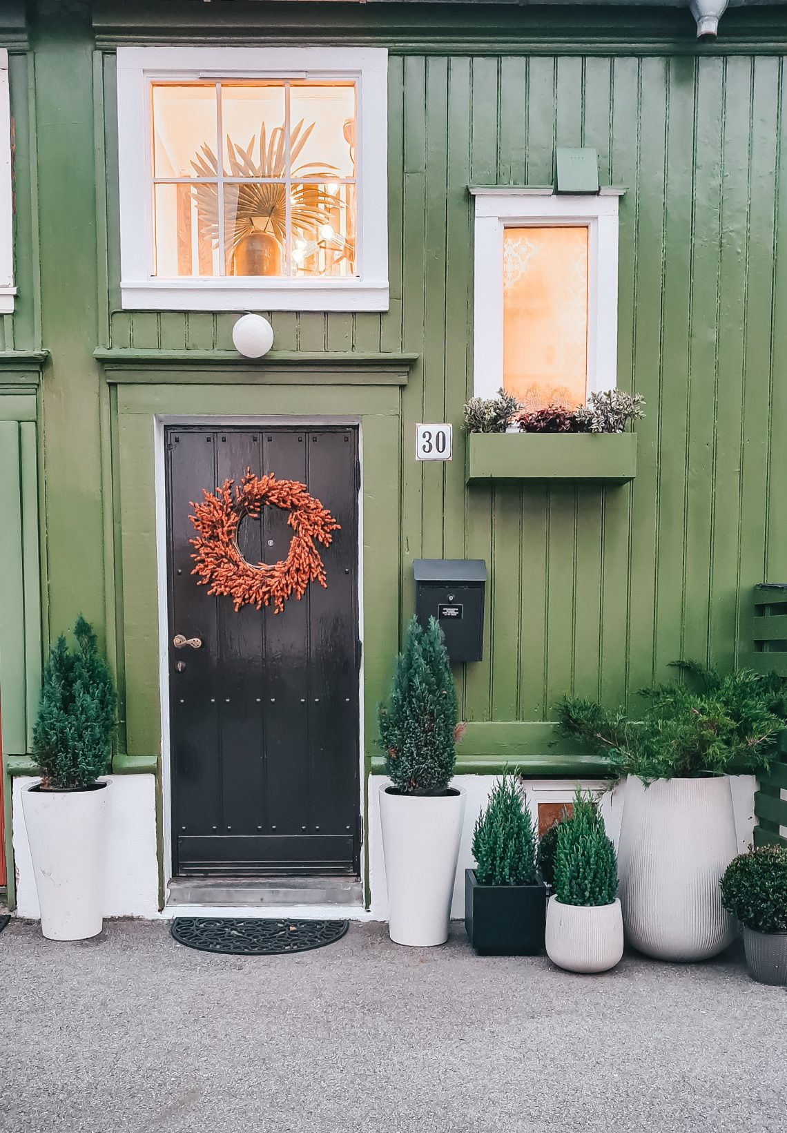 Green Home Exterior - A Gorgeous Norwegian Home Tour You'll Fall In Love With: The green exterior of a homely and gorgeous Scandinavian home. Painted a forest green with box planters below the windows and a black door. Home of Vibeke Sommerbak of Vib Interior #scandinavianinterior #scandinavianexteriorhouse #greenhouseexterior #greenhouseexteriorpaint