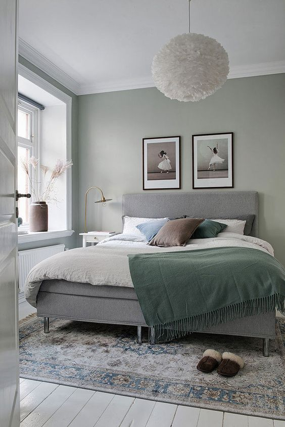 Light Sage Green Bedroom - 8 Of The Best Paint Colours To Try For A Calming Bedroom: A gorgeous and relaxing bedroom painted in a muted sage green colour paired with white and greys makes it an ultimate place for unwinding and getting a good night's rest. #calmingbedroomcolors #mutedgreenbedroom #lightsagegreenbedroom #lightsagegreenbedroomwalls #bedroomcolors #bedroomcolorspaint