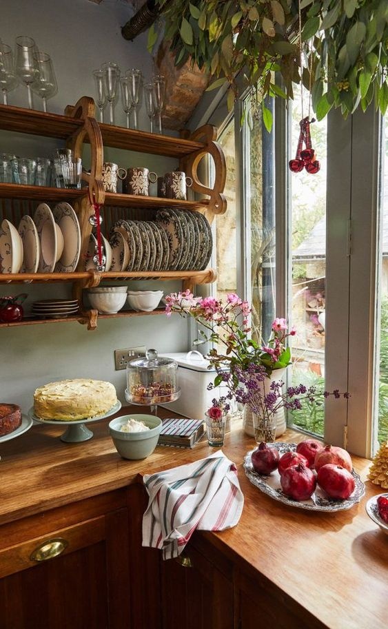 Kitchen Open Plate Rack - 7 Ways To Get The Beautiful Cottagecore Home Aesthetic: Beautiful styled cottage kitchen corner with wooden open shelf rack storage with dish ware and glasses on the wall. Kitchen countertop styled with cakes, fruit and flowers. Interior design Amanda Brooks. #cottagecore #cottagecoreaesthetic #cottagecoreinterior #cottagecoreinteriorkitchen #cottagekitchens #styledkitchencountertop