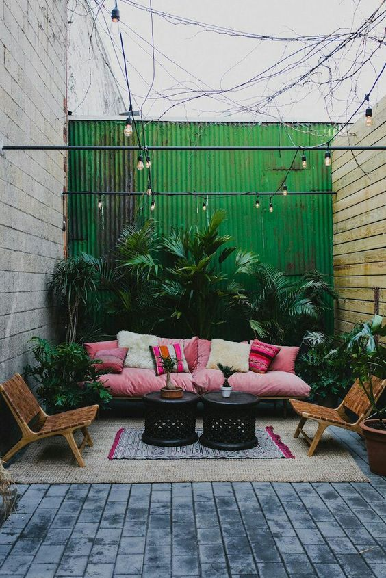 Urban Courtyard Home Garden - 5 Great Design Ideas Worth Incorporating Since Home Lockdown: A tropical styled urban garden courtyard with a green corrugated backdrop decorated with home furniture and potted tropical plants to create an outdoor living area. Garden design unknown. #urbancourtyards #urbancourtyardgarden #urbancourtyardgardenideas #urbancourtyardgardendesign #homegardencourtyard
