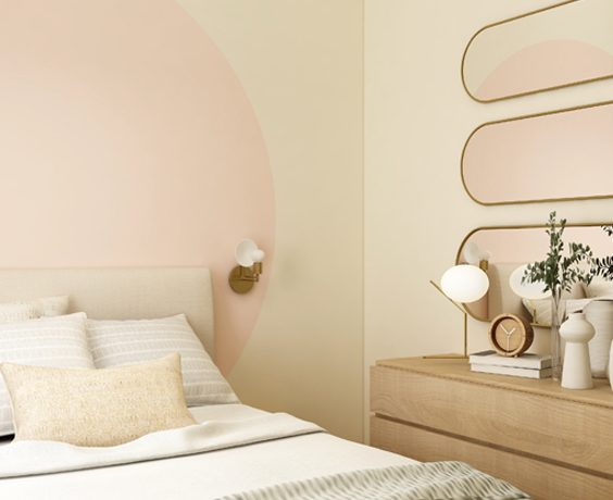 Relaxing Beige and Pink Bedroom - 6 Excellent Reasons Why Decluttering Is Good For You!: A beautiful and organized clutter free bedroom painted in pale pink and beige. With a painted pink circle above the headboard. The bedroom is organized and decorated with accessories making a perfect place to get a good rest at night. #declutter #decluttering #pinkandbeigebedroom #declutteryourhome #benefitsofdecluttering
