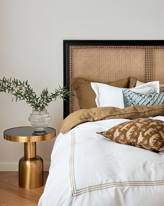 Styled Bed Black Framed Headboard - Stunning Rattan Beds & Headboard Ideas For The Bedroom: A relaxed and modern styled bed with a black framed rattan caned headboard styled with cushions, pillows and a gold nightstand at the side. #rattanbedhead #rattanbedheadstyling #blackrattanbedheadstyling #blackframedheadboard #canedheadboardbedroom #rattanbedroomideas #styledbed