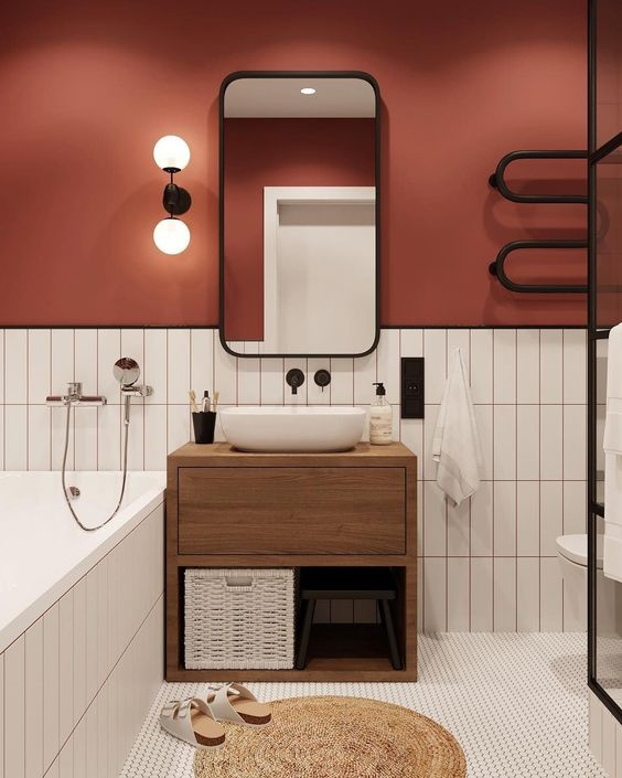 Modern Red and White Bathroom - December Pinterest 2020: Top 15 Ideas & Inspiration: A modern bathroom interior painted a warm rusty red on the top half of walls paired with a white stacked tile on the bottom. With a wooden vanity and black hardware and accessories. #modernbathroom #modernbathroomdesign #redbathroom #redbathroom #redbathroomwalls #redbathroomideas #redandwhitebathroom #stackedwhitetilebathroom
