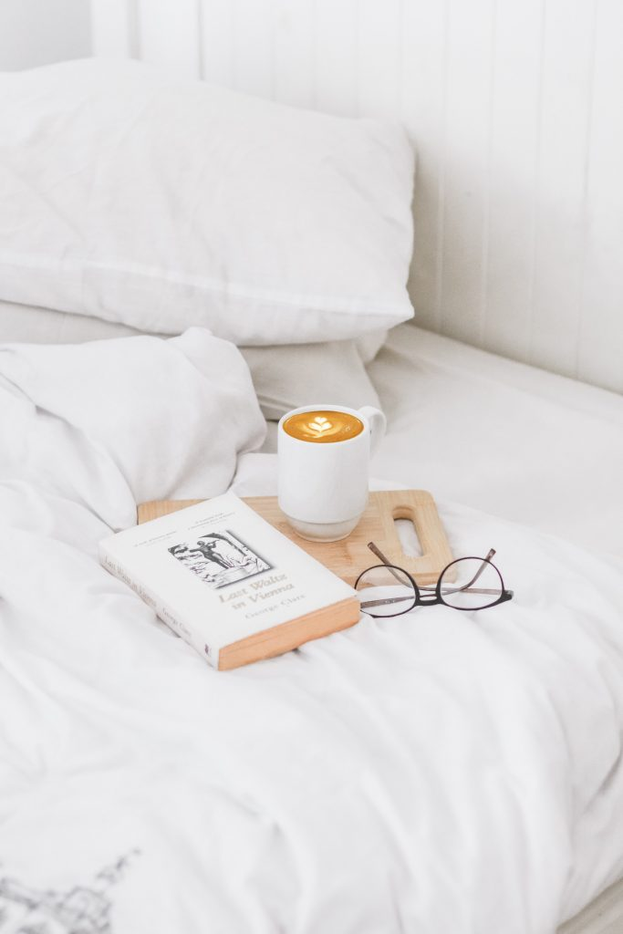 White Bed Linens - 38 Amazing Self Care Ideas To Do Around The Home: White bed linens set with a book and coffee set for a relaxing time of self care at home. Here are some other self care ideas at home, including a free download self care checklist. #selfcare #selfcareathome #whitebedding #selfcareideas #selfcarechecklist #freedownload