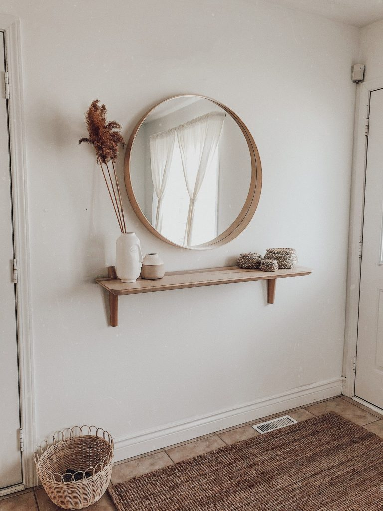 Minimal Hallway Decor - 7 Great Tips To Organize & Style Your Hallway: A hallway entrance with a small space makes the most use by having minimal decor placed on the wall like this wooden mirror and single shelf combo. Interior unknown. #hallwaydesign #hallwaydecor #hallwayideas #minimalhallway #minimalhallwaydecor #minimalhallwaydecorentrance